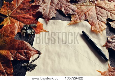 Autumn vintage still life -old paper ink pen on the table among the autumn leaves. Autumn vintage tones processing.Focus at the ink pen.