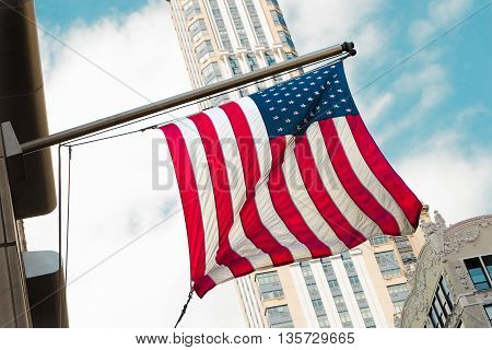 America USA flag waving along building street in New York city to celebrate on Independence Day of the United States, July 4th.