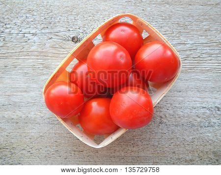 Tomatoes in rattan basket on wood background