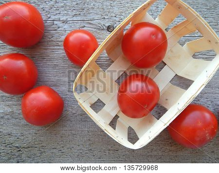 Spilled tomatoes from rattan basket on wood background