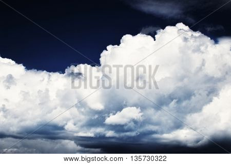 large white clouds on a dark blue sky above Chomutov