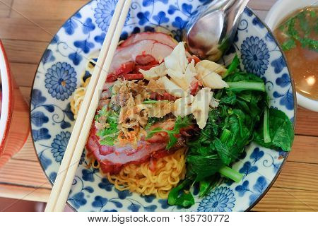 Egg noodles with roasted red pork with crab meat pak choy dish and hot soup in blue and white bowl, metal spoon and wooden chopsticks. Famous Local Thai style street food. flat lay - top view