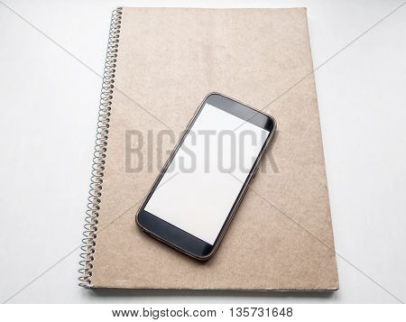 Modern smartphone mockup with white blank screen on kraft notebook cover