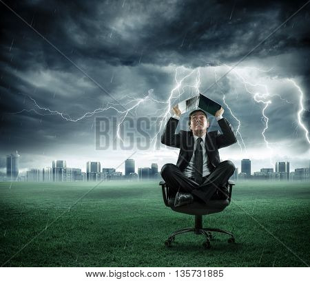 risk and crisis - businessman is repaired by storm with computer