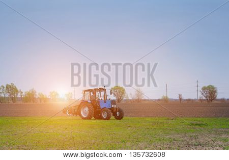 Early at dawn on a spring morning tractor lit by the rays of the sun going to plow the field.
