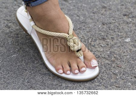 Foot girls fashion sandals with a beautiful pedicure on the road
