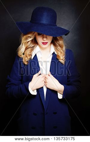 Beautiful woman undresses on Dark Background with blue hat