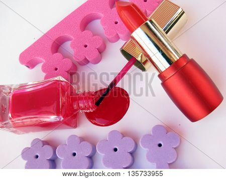 red nail polish and lipstick in same color on white background