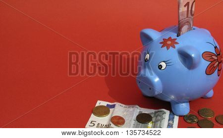 blue piggy bank on red background