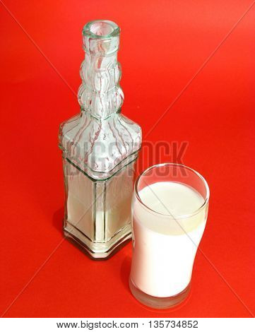 yogurt in bottle and glass on red