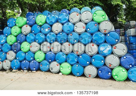 blue grey and green oil barrels on a pile Chemical Plant Plastic Storage Drums