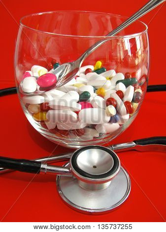 Pills and stethoscope on red background