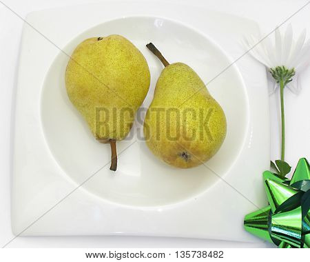 Two healthy pears on white plate and white flower with green ribbon