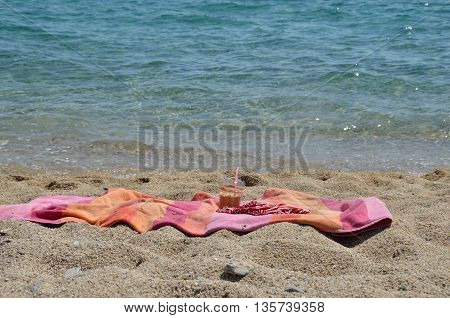 Coffee frappe and pink-orange towel on the beach by the sea