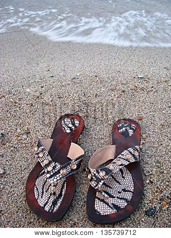 Sand and sea and slippers. Focus on slippers