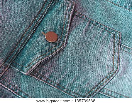 Closeup of green denim jeans pocket.