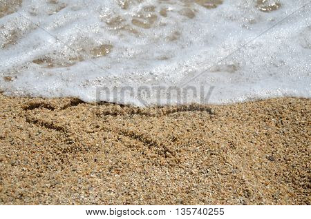 Two heart symbols written in the sandy beach with wave in the sea right behind it