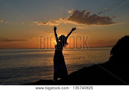 Sunset on sea with silhouette of woman spreading her arms