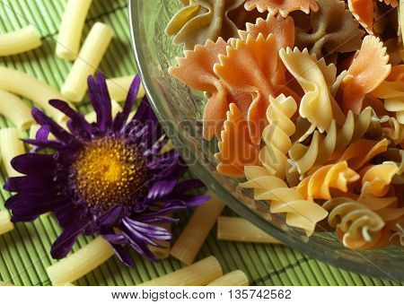 colored pasta  placed in glass plate and flower