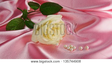 Beautiful rose with pearls on satin