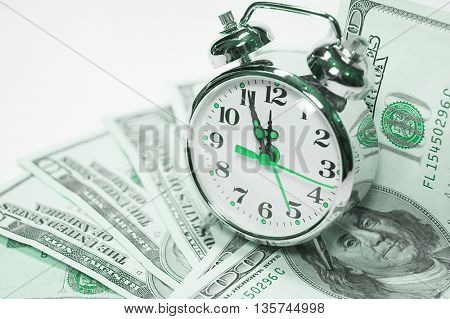 Retro styled alarm clock covered pile of money isolated on white. Time is money concept