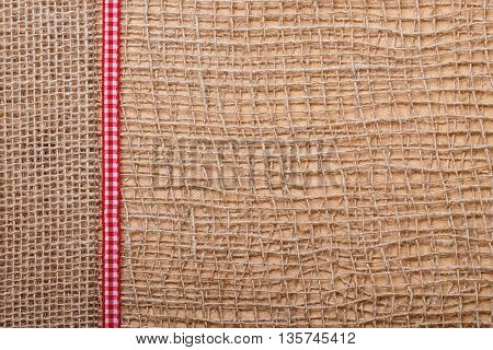 Red Ribbon On Burlap Cloth Background
