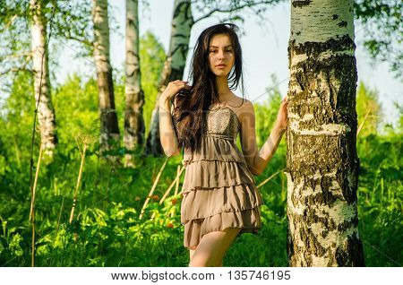 Brunette stands near the birch in forest. girl walking on the green forest. girl in short summer dress in nature . tall and slim girl walking through the forest in a short summer dress