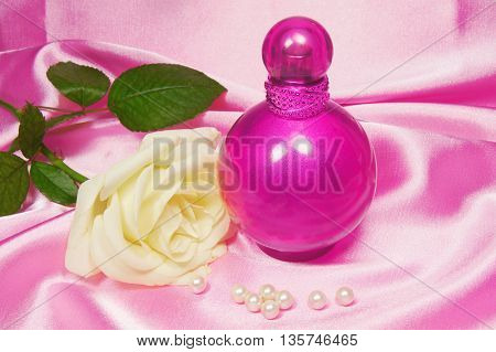 bottle of perfume and white rose