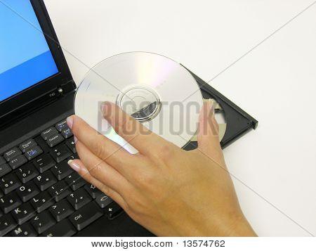 Een foto van een vrouw die het plaatsen van een DVD in een laptop