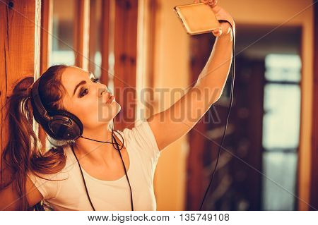Young woman with headphones and smartphone listening to music. Girl relaxing enjoying taking selfie photo. People leisure pleasure concept. Instagram filter.