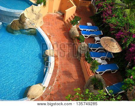 hotel with beautiful swimming pool surrounded by chairs and flowers