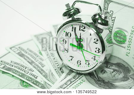 Retro styled alarm clock covered pile of money isolated on white. Time is money concept , dollars, euro