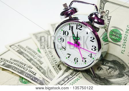Retro styled alarm clock cover pile of money isolated on white. Time is money concept , dollars, euro