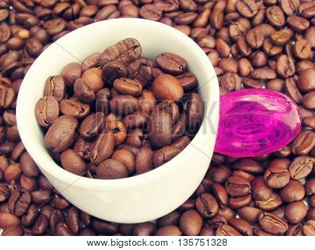 Cup of coffee. contains lot of beans, in pastel colors.