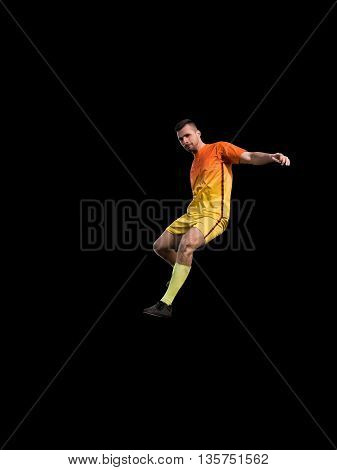 Professional football player in red uniform on training black background