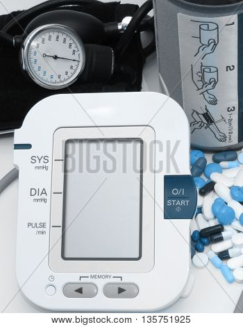 pills and old and new version of blood pressure measuring device