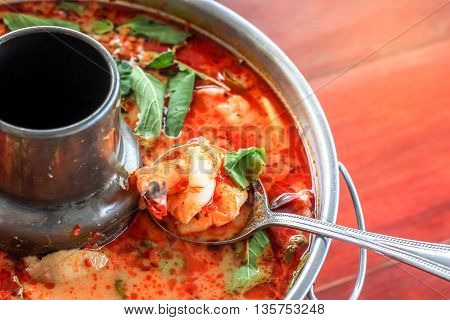 Top view spicy tom yum goong Thai style in the hot pot spicy soup a classic spicy lemongrass and shrimp soup recipe from Thailand