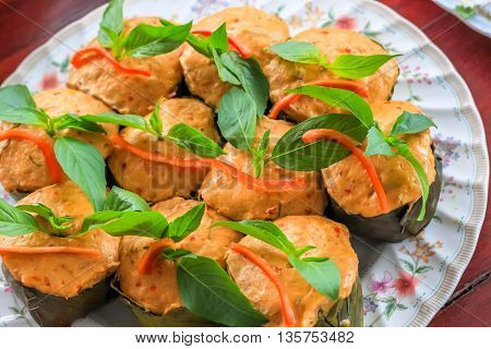 Top view Thai steamed curry fish in banana leaf cups decorated with basil leaf (Hor Mok Pla)
