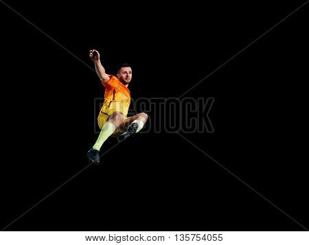Professional football player in red uniform in jump on training black background