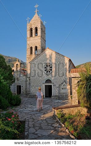 a woman is entering the Church of Rezevici Monastery, Montenegro