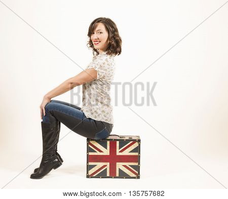Beautiful young woman sitting on a vintage suitcase smiling, studio shot on white background. Ready for adventure