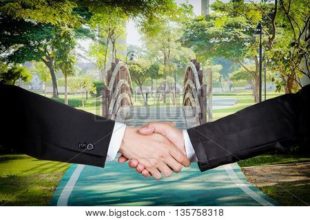 Businessmen shaking hands with a small curved wooden bridge in the garden background.