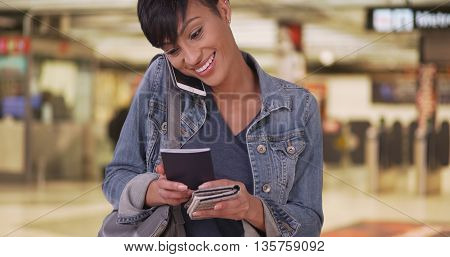 Woman Talking On Cellphone And Holding Passport In Airport Terminal While Waiting For Flight
