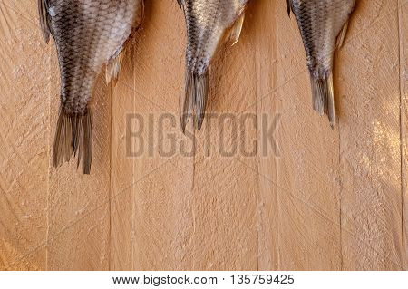 Tails Of Dried Fish On A Wooden
