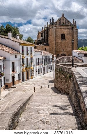 Cobble stone street in Ronda Andalucia Spain leading to a church.