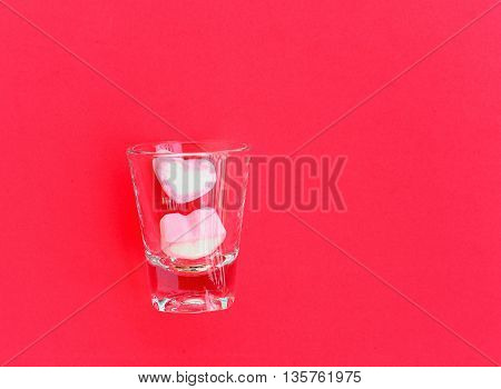heart shape marshmallows in shot glass on red background