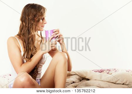 Relax home happiness and people concept. Young woman sleepy girl sitting relaxing on bed at morning with cup of tea coffee