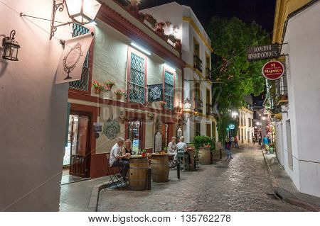 street view of summer evening in Cordoba Spain. people enjoy outdoor restaurant drinking and chatting