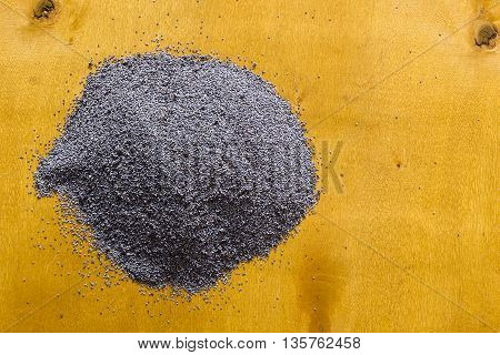 Raw poppy seeds on a yellow wooden background
