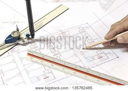 hand holding pencil point to architectural plans project drawing architect engineering and contractor concept